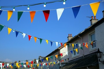 Bright colorful bunting or pennant flags hanging across pretty village street against blue sky for a traditional celebration, multi coloured.