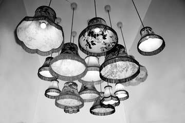 Antique or vintage lampshades hanging in a display group, with black and white monochrome filter