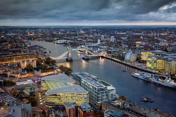 Fotomurales - Luftaufnahme der Tower Bridge und Skyline von London mit den beleuchteten Häusern an einem bewölktem Herbst Abend, Großbritannien