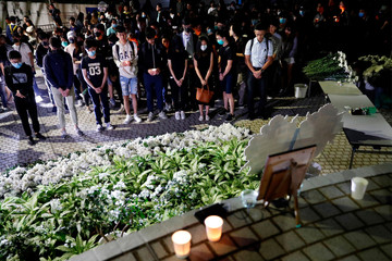 People pay tribute with flowers to Chow Tsz-lok, 22, a university student who fell during protests at the weekend and died early on Friday morning, at the Hong Kong University of Science and Technology, in Hong Kong