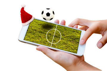 man hand hold and touch screen smartphone with Christmas hat and football field on screen ,image for  sport football or soccer online gambling on holiday.