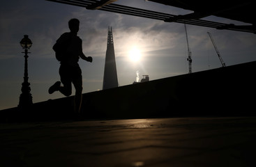 A man jogs past the Shard at sunrise in London