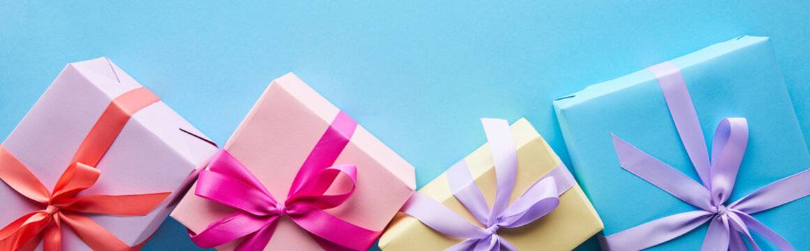 top view of colorful gift boxes on blue background, panoramic shot