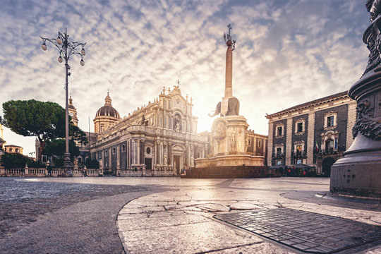 """Catania Dome Square at the sunset and the famous landmark elephant fountain also know as """"liotru"""" by the indigenous people. Cloudy sky and marvelous sun light."""