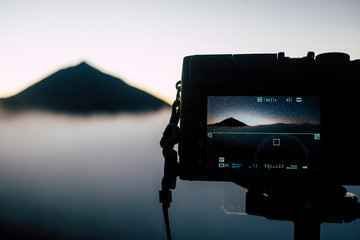 Close up of photography display camera showing beautiful landscape taken and exif of he pictures -technical details of shooted pict - technology and nature outdoor leisure activity