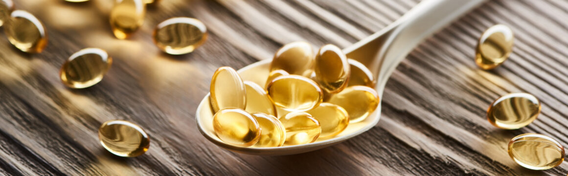 golden fish oil capsules in spoon on wooden table, panoramic shot