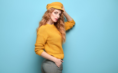 Fashionable woman in Trendy orange outfit, stylish hairstyle, makeup. Young redhead in jumper, yellow cap. Sensual beautiful model girl in stylish pants, fashion beauty concept on blue Wall mural