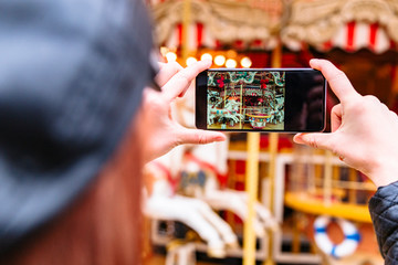 Girl takes pictures of carousel and horse figure