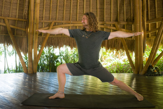 young attractive and happy man in hipster yogi style doing yoga drill on mat at beautiful Asian bamboo hut stretching body enjoying nature in mind balance