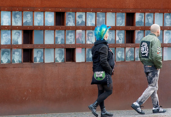 People watch photographs of victims killed at the Wall, at the Berlin Wall memorial on Bernauer Strasse in Berlin