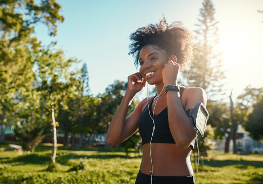 Happy young black african american woman enjoying listening to music on earphones while jogging workout in the bright sunlight at park