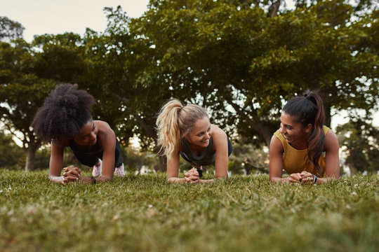 Three sporty young women smiling while doing plank exercises lying on green grass in the park