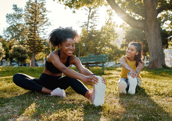 Young diverse female friends sitting on green grass stretching her legs in the morning sunlight at park - diverse friends warming up before doing group exercise  - fototapety na wymiar