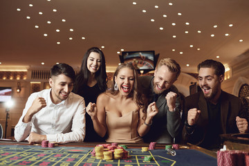 Fototapeta Happy people are betting in gambling at roulette poker in a casino