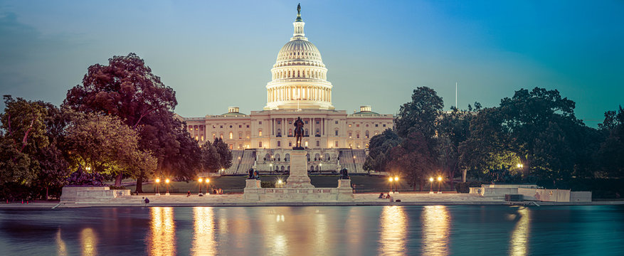 Panorama of the Capitol of the Unites States in evening light with the Capitol Reflecting Pool in the foreground.