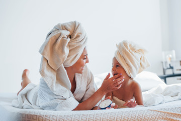 Using cream. Young mother with her daugher have beauty day indoors in white room