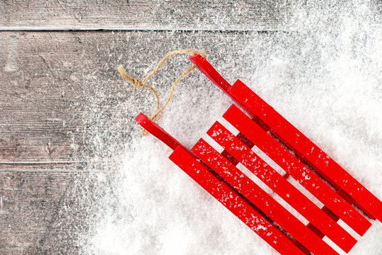 Red Sledge in Snow and on Brown Wood