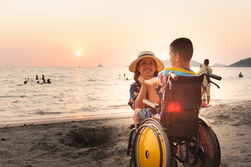 Mother and Asian special child on wheelchair is happily on the beach,Mom and son spend holiday to travel and learning about nature around the sea,Life in the education age, Happy disabled kid concept.