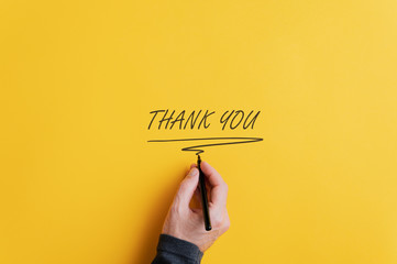 Male hand writing a Thank you sign