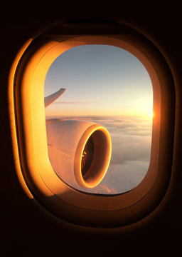 View out of an airplane window of the jet's wing and engine with a stunning sunset