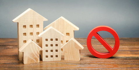 Wooden houses and a prohibition sign. Inaccessible and expensive housing. Restrictions and a ban on the construction of buildings. Interdictions within settlements. Inaccessibility Index
