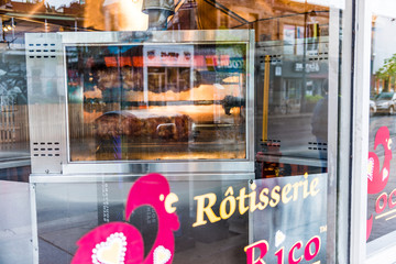 Montreal, Canada - May 26, 2017: Rotisserie chicken machine with many plump birds roasting outside restaurant
