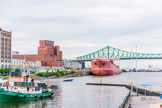 Montreal, Canada - May 27, 2017: View of old port area with large red ship and Molson factory in city in Quebec region during sunset