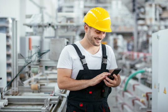 Factory worker in uniform with phone