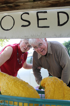 Retired man and woman buying squash at roadside stand