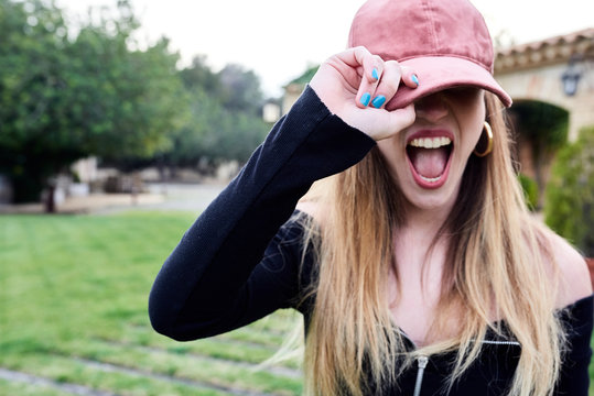 Girl in cap shouting out outdoors.