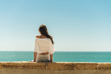 brunette sitting on the parapet with her back to the camera on the background of the ocean, legs dangling from the parapet