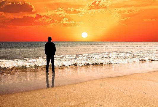hombre en la playa mirando el atardecer