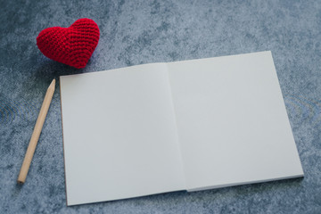 Pencil and plain notebook with red heart symbol black background with copy space. Concept of quotes and note down diary, lovely story and romantic relationship of lover or family. Happy Vanlentine