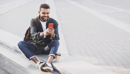 Young handsome men using smartphone in a city. Smiling student man texting on his mobile phone. Coffee break. Modern lifestyle, connection, business concept Fotobehang