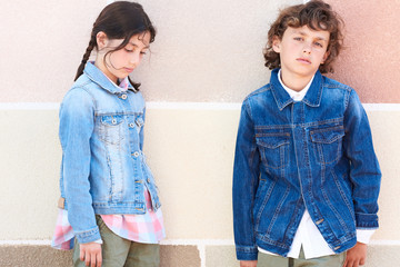 Girl with braids and boy with curly hair in denim jackets.