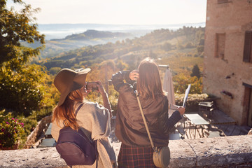 Womans enjoying a sunny day on travel and take picture on landscape