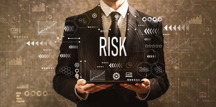 Risk with businessman holding a tablet computer on a dark vintage background