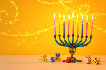 religion image of jewish holiday Hanukkah background with menorah (traditional candelabra)and spinning top over yellow background