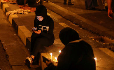 Demonstrators light up candles for the people killed at an anti-government protest in Iraq, in Baghdad