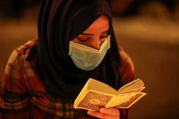 An demonstrator reads Quran for the people killed at an anti-government protest in Iraq, in Baghdad