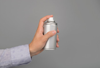 hand holds aerosol spray can
