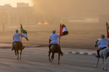 Foto auf AluDibond Drachen Largest Military Show at Marjan Island with coordinated military event with horses riding down the street and UAE flags landing in the sunset smoky haze