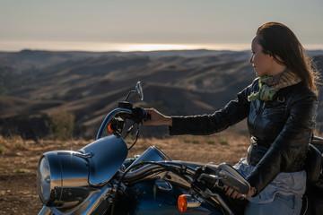 Woman biker sitting on her motorcycle