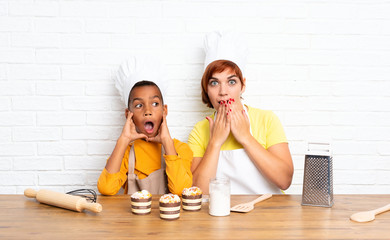 Mother and her son dressed as chef in a kitchen and doing surprise gesture