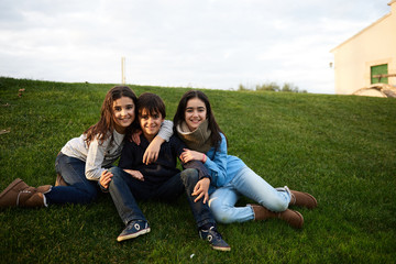 Three friends sitting and hugging on garden at their home
