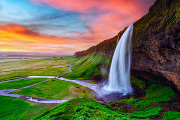 Photo sur Aluminium Cascades Sunrise on Seljalandfoss waterfall on Seljalandsa river, Iceland, Europe. Amazing view from inside. Landscape photography