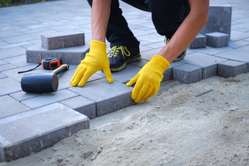 The master in yellow gloves lays paving stones in layers. Garden brick pathway paving by...