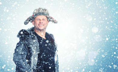 Happy smiling man in open winter clothes rejoices in falling snow
