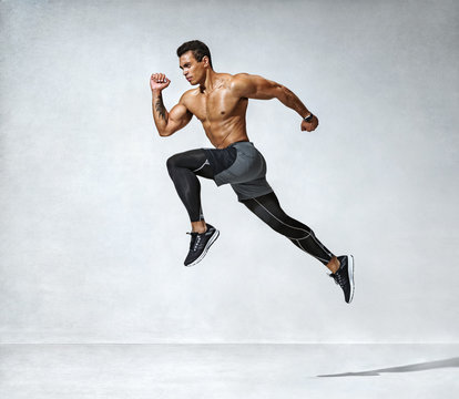 Sporty man jumping. Photo of active man with naked torso on grey background. Dynamic movement. Side view. Sport and healthy lifestyle