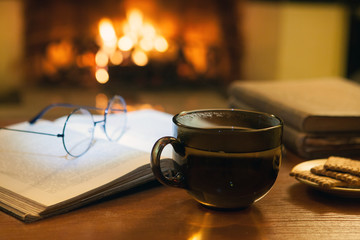 An open ancient book, vintage glasses, a cup and biscuits in front of the fireplace. Evening fairy tales. Fantasy.